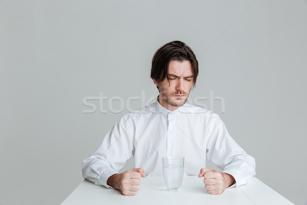 Angry frustrated man sitting at the table with water glass Stock photo © deandrobot