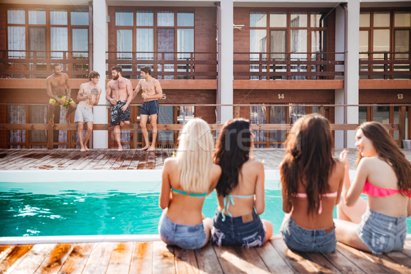 Women sitting near swimming pool and looking at attractive men Stock photo © deandrobot