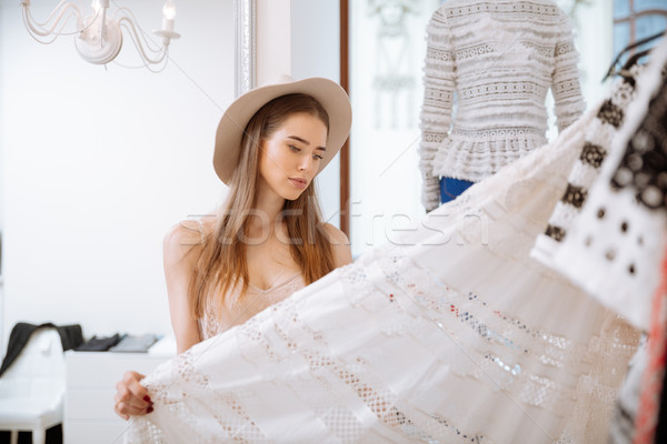 Stock photo: Pensive woman standing and choosing skirt in clothing store