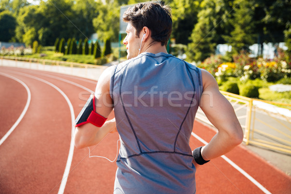 Back view of a runner listening music with mobile phone Stock photo © deandrobot
