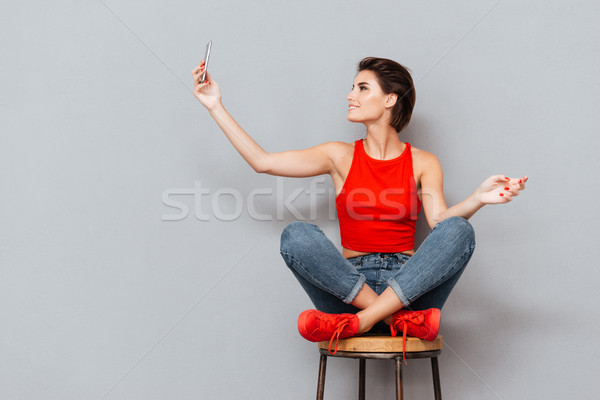 Smiling young woman making selfie photo on smartphone Stock photo © deandrobot