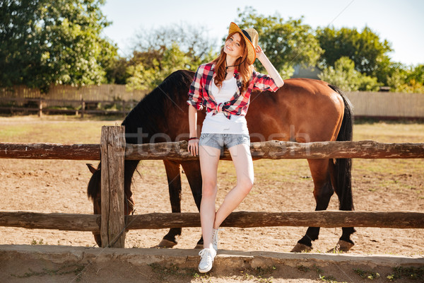 Beautiful young woman cowgirl staning with her horse on ranch Stock photo © deandrobot