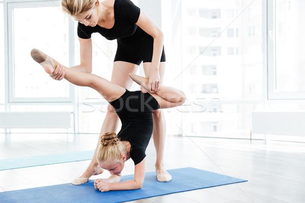 Női tánc tanár nyújtás kicsi tornász Stock fotó © deandrobot