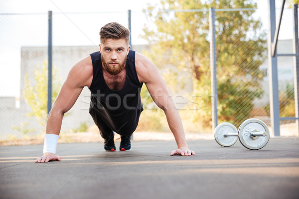 Portrait of a concentrated man athlete doing plank exercise outdoors Stock photo © deandrobot