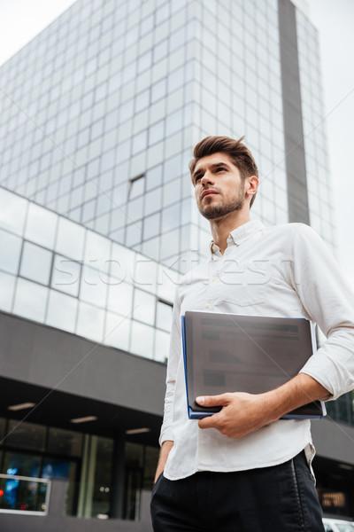 Businessman holding folder with documents standing near business center Stock photo © deandrobot