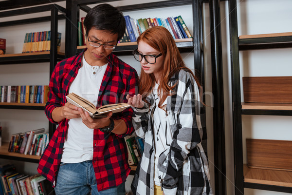 Concentrated young man and woman reading book in library Stock photo © deandrobot