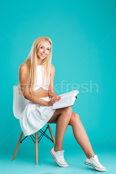 Smiling young woman holding opened book and sitting on chair Stock photo © deandrobot