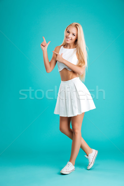 Smiling attractive young woman pointing two fingers away Stock photo © deandrobot