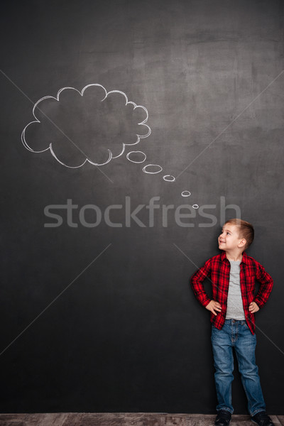 Kid thinking with thought bubble at chalkboard, looking on painting Stock photo © deandrobot