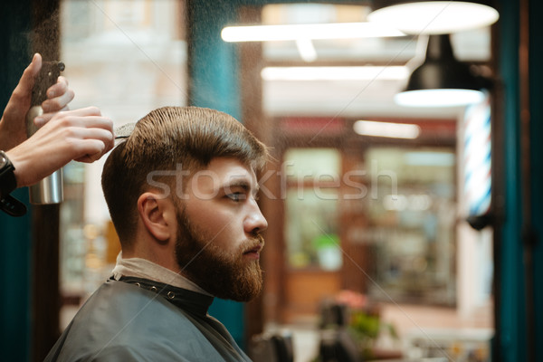 Handsome man getting haircut by hairdresser while sitting in chair. Stock photo © deandrobot