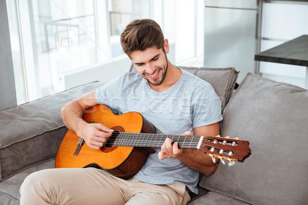 Hombre jugando guitarra sesión sofá casa Foto stock © deandrobot