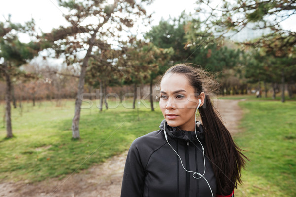 Female attractive runner in warm clothes and earphones Stock photo © deandrobot