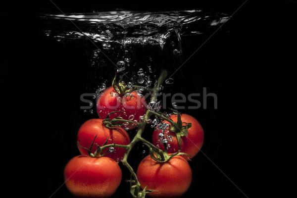 Fresh tomato dropped into water Stock photo © deandrobot