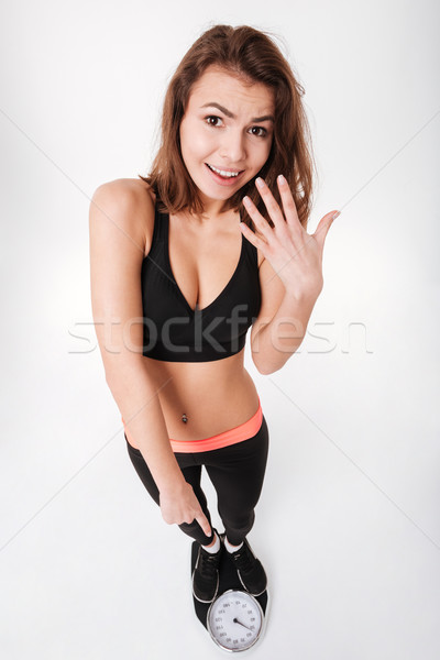 Amazed pretty young sportswoman standing and pointing on weighting scale Stock photo © deandrobot