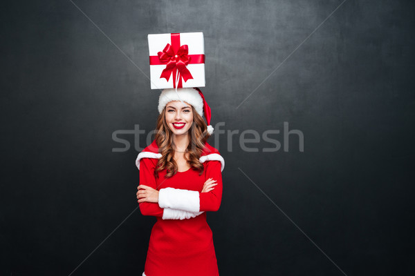 Woman with gift box on her head and arms folded Stock photo © deandrobot