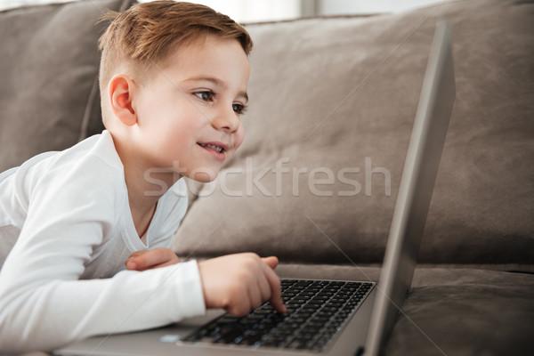 Alegre nino usando la computadora portátil ordenador mentiras sofá Foto stock © deandrobot