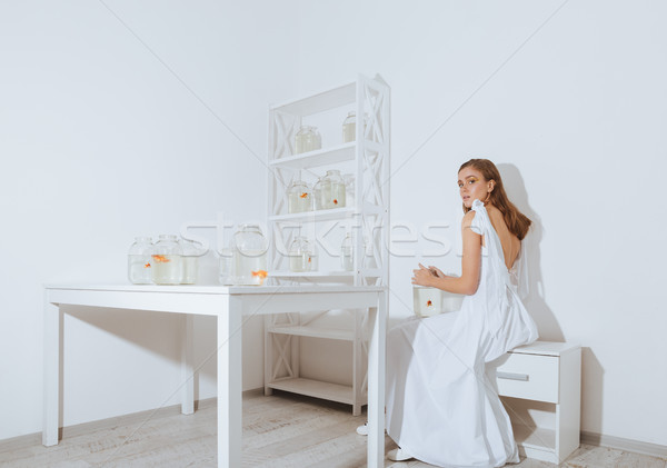 Attractive young woman with gold fish in jar Stock photo © deandrobot