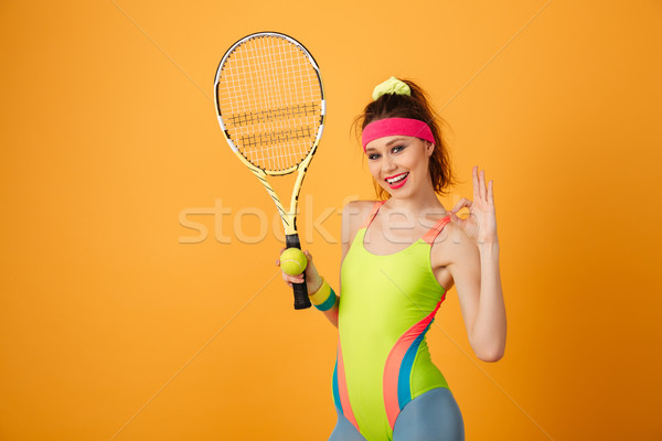 Cheerful sportswoman with tennis racket and ball showing ok sign Stock photo © deandrobot