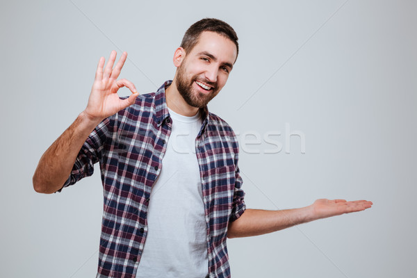 Bearded man showing ok sign and holding on pound Stock photo © deandrobot
