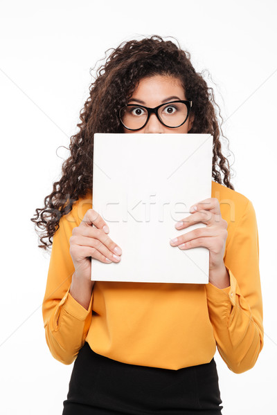 Embarrassed african young businesswoman hiding her face behind blank paper Stock photo © deandrobot