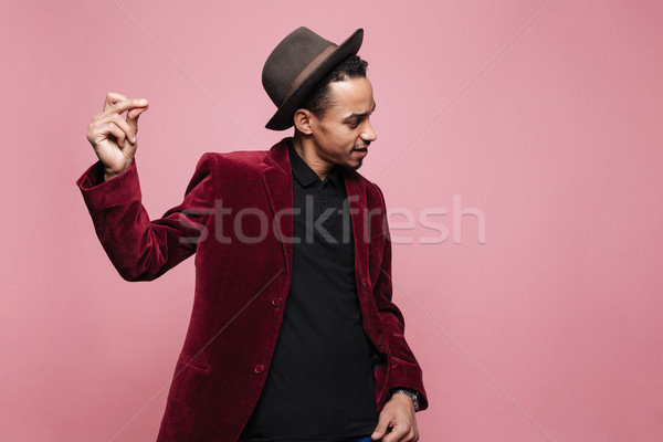 Portrait of a young african man in hat and jacket dancing Stock photo © deandrobot