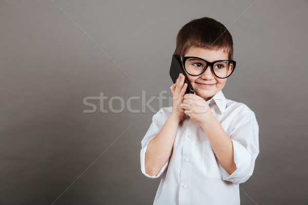 Cheerful little boy businessman in glasses talking on cell phone Stock photo © deandrobot