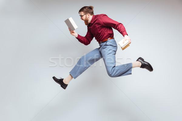 Masculino nerd saltando livros estúdio mãos Foto stock © deandrobot
