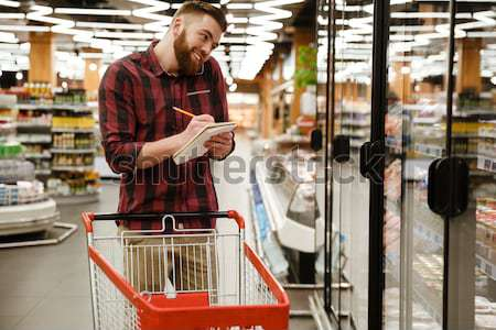 Stock photo: Cheerful young man standing in supermarket talking by phone.