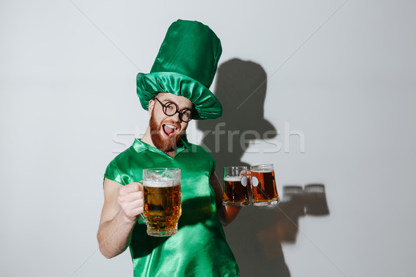 Screaming happy man in st.patriks costume holding cups Stock photo © deandrobot
