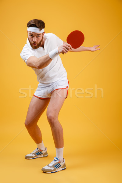 Concentrated emotional young sportsman holding racket for table tennis. Stock photo © deandrobot