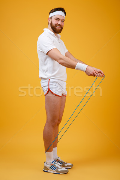 Cheerful young sportsman holding skipping rope Stock photo © deandrobot
