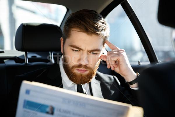 Serious business man reading newspaper Stock photo © deandrobot