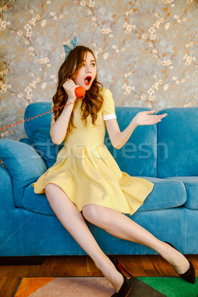 Shocked young pin-up lady talking by phone. Stock photo © deandrobot