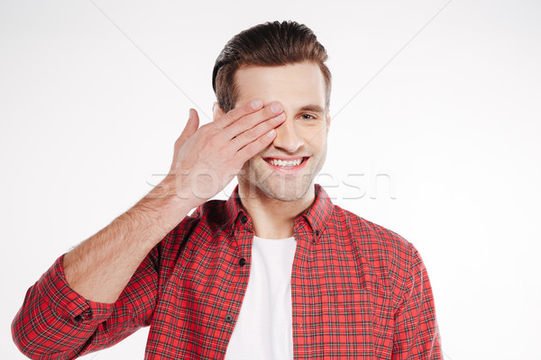 Smiling Man covering one eye Stock photo © deandrobot