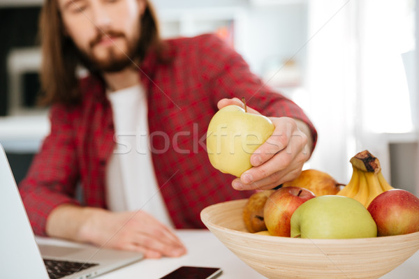 Closeup of man eating fruits and using laptop at home Stock photo © deandrobot