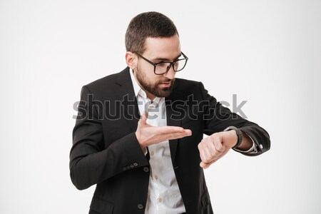 Young bearded businessman looking at watch. Stock photo © deandrobot