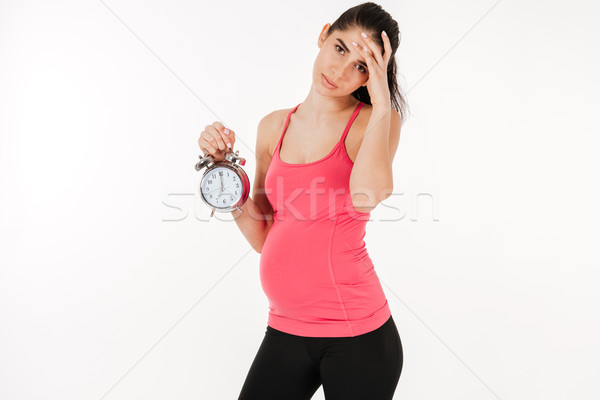 Hamile kadın çalar saat genç yalıtılmış beyaz Stok fotoğraf © deandrobot