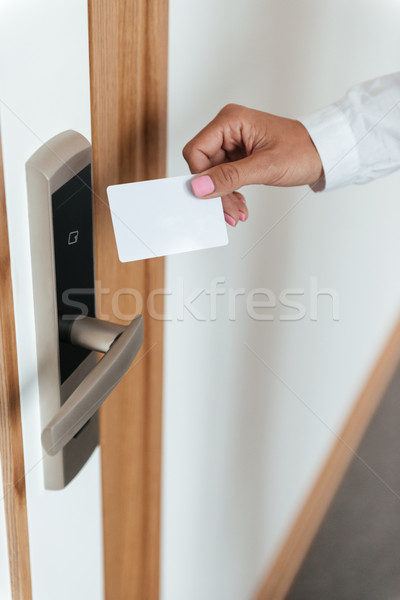Woman hand inserting key card in electronic lock Stock photo © deandrobot