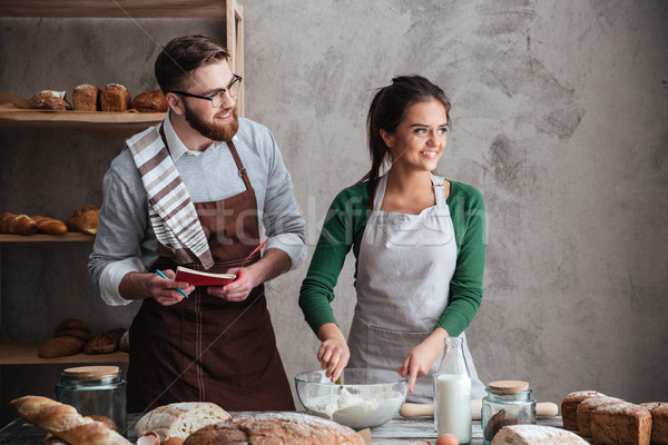 Cute family looking away while cooking bread Stock photo © deandrobot