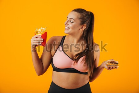 Happy smiling girl in swimsuit holding pineapple and coconut Stock photo © deandrobot