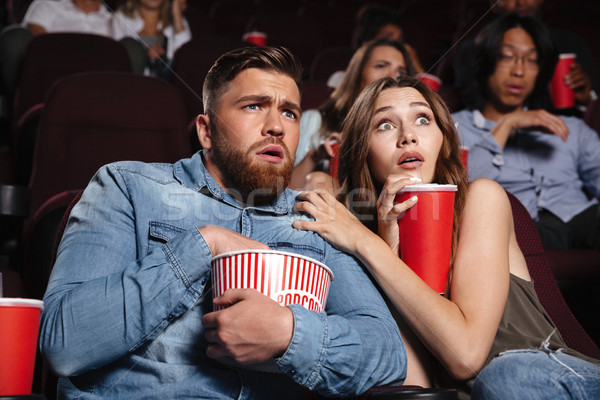 Young scared couple watching a horror movie Stock photo © deandrobot