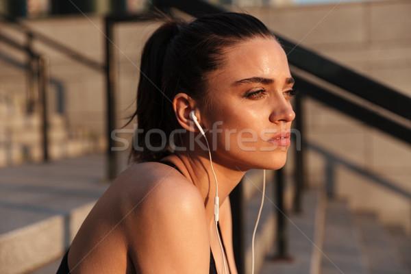 Komoly fiatal sportok hölgy ül fülhallgató Stock fotó © deandrobot