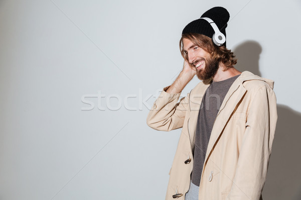 Handsome hipster man looking aside listening music with headphones. Stock photo © deandrobot