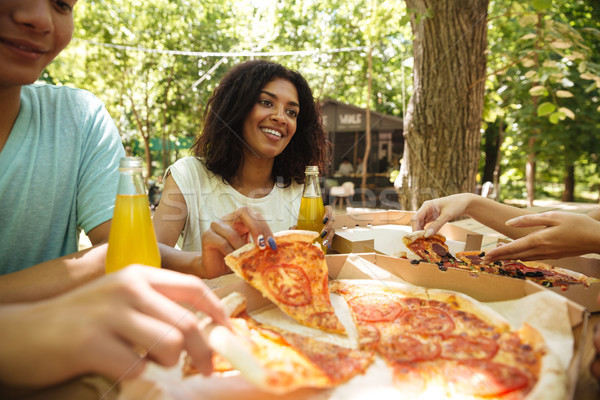 Friends sitting by the table in forest Stock photo © deandrobot