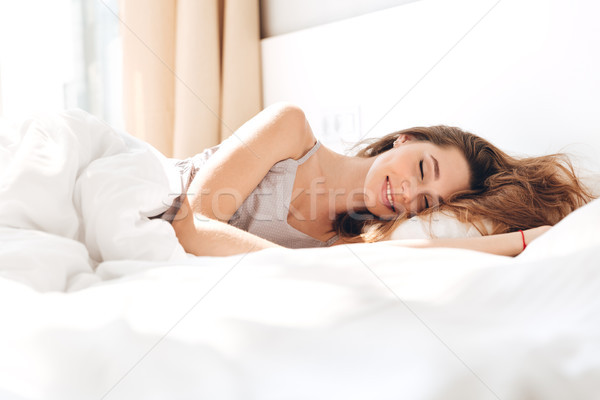 Smiling pretty lady lies in bed indoors. Eyes closed. Stock photo © deandrobot