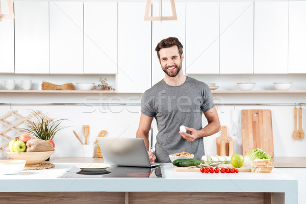 Attractive young man cooking with mixing bowl Stock photo © deandrobot