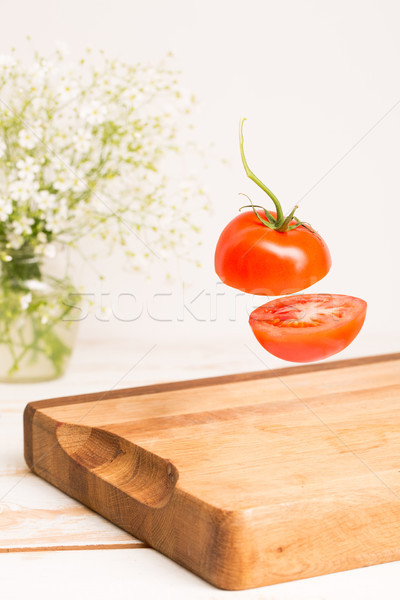 Sliced whole tomato flying above a wooden chopping board Stock photo © deandrobot