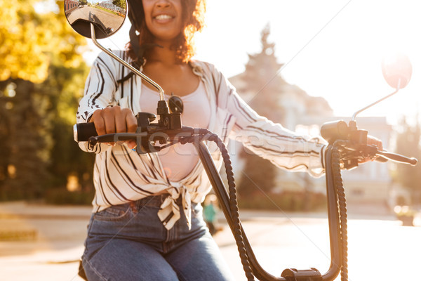 Cropped image of smiling african woman sitting on modern motorbike Stock photo © deandrobot