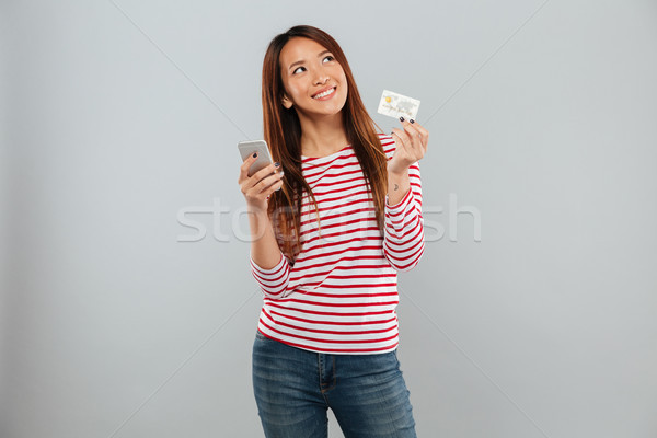 Smiling pensive asian woman holding smartphone and credit card Stock photo © deandrobot
