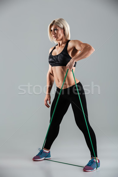 Side view photo of sports woman exercising with resistance band Stock photo © deandrobot